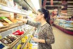 食谱成份的少妇购物在一个大超级市场 购物杂货、家庭、健康和秀丽 自已服务 免版税图库摄影