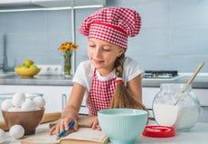 读食谱的小女孩 免版税库存图片