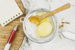 食谱的笔记本,鸡蛋,在面粉背景的木匙子  库存照片