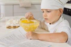 读食谱的逗人喜爱的小男孩,他烹调 免版税图库摄影