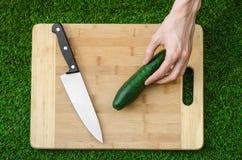 素食主义者和烹调在题材的本质:拿着一个刀子和黄瓜在切板和背景的人的手 免版税图库摄影