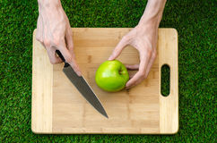 素食主义者和烹调在题材的本质:拿着一个刀子和绿色苹果在切口公猪的背景的人的手 图库摄影