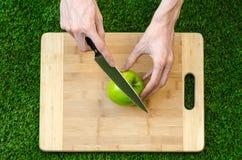 素食主义者和烹调在题材的本质:拿着一个刀子和绿色苹果在切口公猪的背景的人的手 免版税库存图片