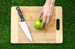 素食主义者和烹调在题材的本质:拿着一个刀子和绿色苹果在切口公猪的背景的人的手 库存照片