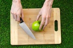 素食主义者和烹调在题材的本质:拿着一个刀子和绿色苹果在切口公猪的背景的人的手 免版税库存照片