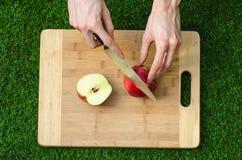 素食主义者和烹调在题材的本质:拿着一把刀子和一个红色苹果在切口公猪的背景的人的手 库存照片