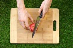 素食主义者和烹调在题材的本质:拿着在绿色g背景的人的手一个刀子和蕃茄切板  免版税库存图片