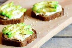 素食主义者在一个木板的鲕梨和hummus三明治 快和健康单片三明治 吃健康 不食肉的膳食 特写镜头 库存照片