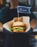 素食主义者快餐-与文本标签的汉堡在手上 免版税库存照片