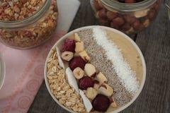 素食主义者早餐与Chia的香蕉圆滑的人,椰子,樱桃,坚果,燕麦粥 库存照片