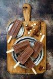 素食主义者香蕉与自创榛子传播的巧克力软糖冰棍儿 乳脂状的牛奶店自由冰流行, nicecream, fudgesicles 库存图片