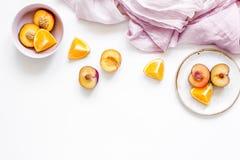 餐巾、被切的桃子和桔子异乎寻常的果子的在白色背景顶视图大模型 免版税库存图片