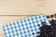 餐巾白色和蓝色与咖啡豆右边 复制空间木桌 图库摄影