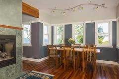 餐桌和椅子与木地板、被绘的墙壁、口音照明设备和看法窗口在当代高级家庭内部 免版税库存照片