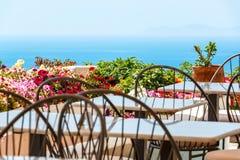 餐馆书桌和椅子在海附近 免版税库存照片