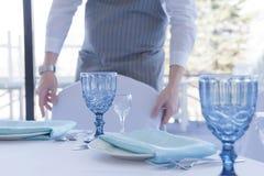 餐馆侍者服务一次婚姻的庆祝的一张桌,移动椅子 免版税图库摄影