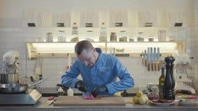 餐馆制服的厨师人和黑手套在有许多厨房用具的现代厨房里站立和 影视素材