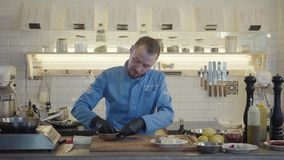 餐馆制服的厨师人和黑手套在有许多厨房用具的现代厨房里站立和 股票视频