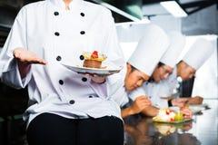 餐馆厨房烹调的亚裔厨师 免版税库存照片