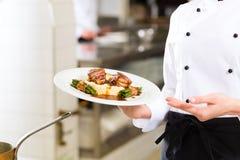 餐馆厨房烹调的女性厨师 免版税库存照片