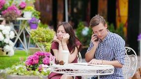 餐馆在室外咖啡馆的游人夫妇 女孩哀伤在她的男朋友,因为他是繁忙的与差事 股票录像