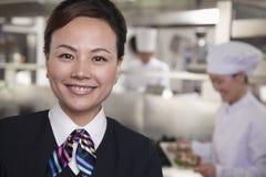 餐馆女主人在一个工业厨房里 免版税库存图片