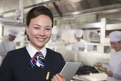 餐馆女主人在一个工业厨房里 库存图片