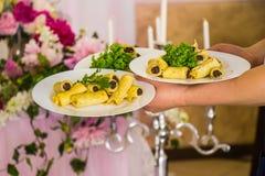 餐馆承办酒席服务 有食物盘服务宴会桌的女服务员 免版税库存照片