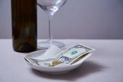 餐馆技巧或小费 钞票和硬币在板材 免版税图库摄影