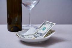 餐馆技巧或小费 钞票和硬币在板材 库存图片