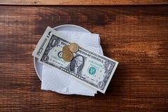 餐馆技巧或小费 钞票和硬币在板材 免版税库存图片