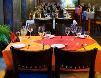 餐馆服务的表 在红色橙色餐巾的银器、陶器和厨房器物 经典内部餐馆 免版税库存照片