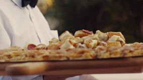 餐馆服务宴会的一位年轻侍者,交付在一块大木板材的可口意大利盘,在慢 股票录像