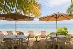 餐馆桌和太阳懒人在海滩 免版税库存图片