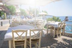 餐馆桌和椅子在遮光罩下在大阳台在海滨 餐馆的被弄脏的场面Neos marmaras的, 库存照片