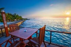 从餐馆的美好的日落海滩的 热带海岛w 免版税库存照片