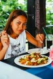 餐馆的年轻亚裔妇女吃混乱油炸物米线用肉和菜,菲律宾食物电话pansit bihon的 库存图片
