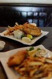 餐馆被镀的盘,炸鱼加炸土豆片膳食 图库摄影