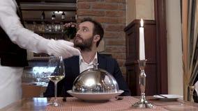 餐馆访客在照相机前面坐 侍者打开碗筷盖子-显示盘的钓钟形女帽 美好的用餐的restaura 股票录像