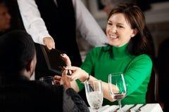 餐馆:妇女采取晚餐的比尔 免版税库存照片