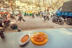 饥饿的人民向在街道咖啡馆的晚餐求助用印地安食物biryani米和dal汤 图库摄影