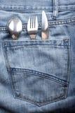 饥饿的人运载一把叉子、匙子和刀子入后面口袋 库存照片