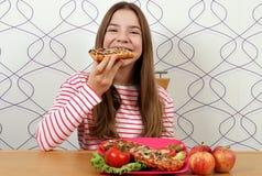 饥饿的十几岁的女孩吃三明治 库存照片