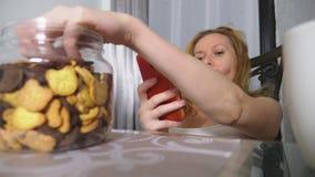 饥饿的哀伤的妇女在客厅坐在桌上在晚上,她吃肝脏并且使用她的智能手机 股票视频