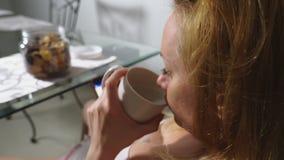 饥饿的哀伤的妇女在客厅坐在桌上在晚上,她吃肝脏并且使用她的智能手机 股票录像