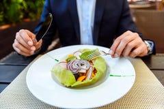 饥饿的商人吃健康昂贵的食物 库存图片