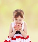 饥饿的女孩咬住苹果 免版税库存图片