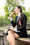 饥饿的女实业家在公园 免版税库存图片