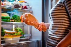 饥饿的妇女在他的手和身分上的其次握火鸡腿 免版税库存图片