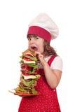 饥饿的小女孩厨师吃三明治 库存照片